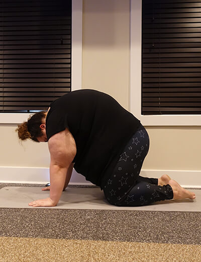 plus size woman doing yoga cat pose