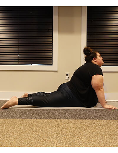 plus size woman doing yoga cobra pose
