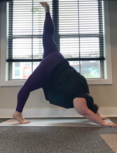 plus size woman doing yoga downward dog