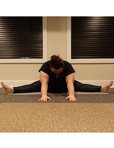plus size woman doing yoga forward fold