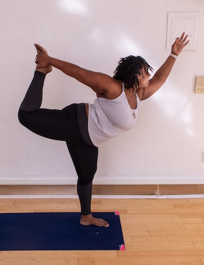 Deanna, Black plus size yoga teacher shows off a challenging pose.