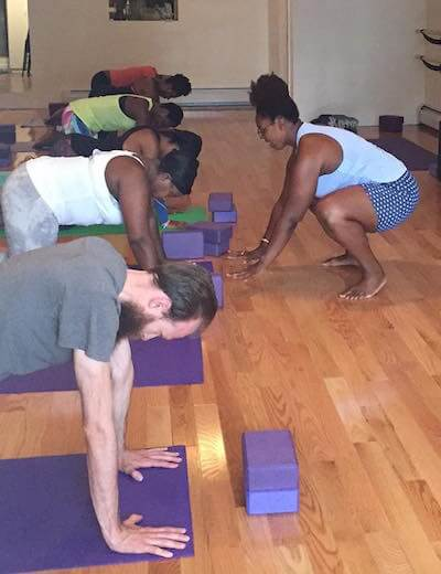 Deanna, Black plus size yoga teacher leads her students in a pose.