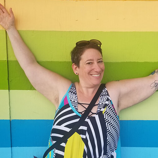 deb malkin body-positive massage therapist in front of striped wall