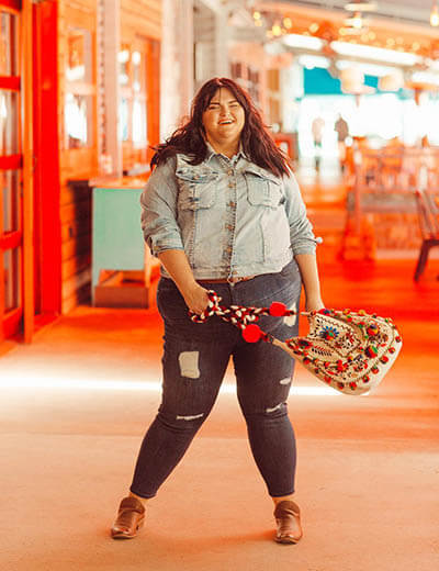plus-size outfit photos denim jacket distressed jeans pom pom bag