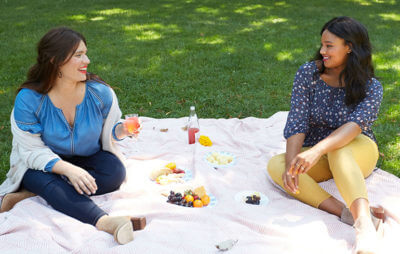 Plus size models having a picnic in the park.