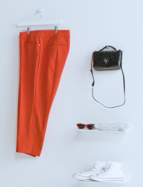 plus-size red pants on wall next to purse sunglasses and shoes