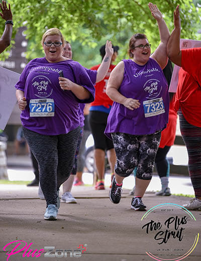 the plus size 5k women smiling and high fiving