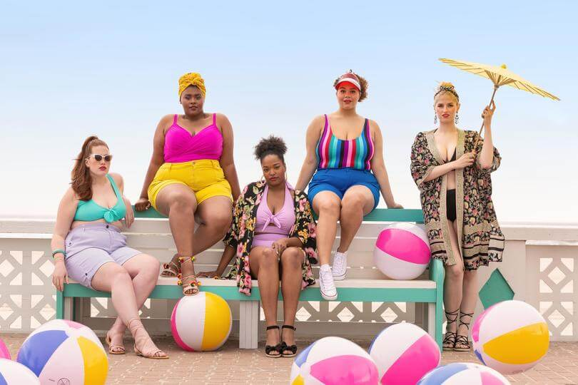 Plus size models wearing swimwear and cover ups at the beach