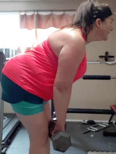 plus size woman in red tank top and shorts using weights