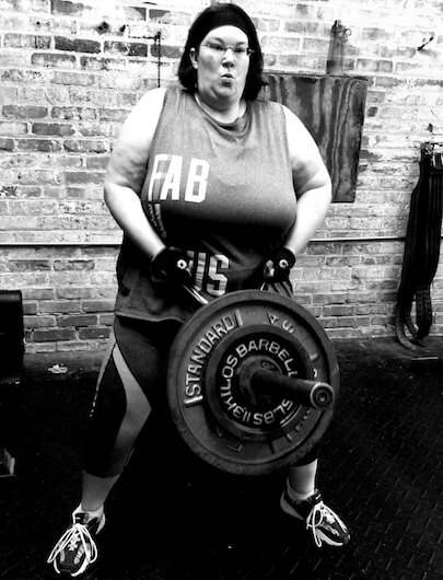 plus size woman lifting a weight