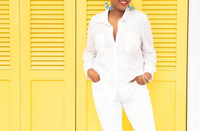 plus-size model wearing a white top and white jeans with bold jewelry.