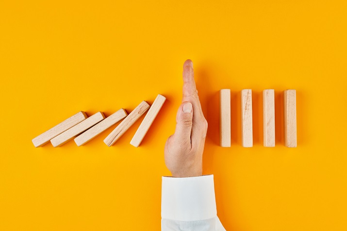 Hand of a businessman stopping domino effect on yellow background