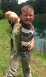 Johnny Casey, age 6, of Ravenswood, W.Va. with his first ever bass caught from a farm pond in Mason County, W.Va.