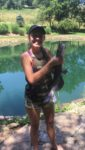 Summer Blosser of Morgantown shows off a catfish caught from a Monongalia County farm pond.