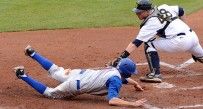 West Virginia catcher Alan Filauro can't tag Kansas runner Kevin Kuntz as the Jayhawks took a two-run first-inning lead. KU won the game 7-2.