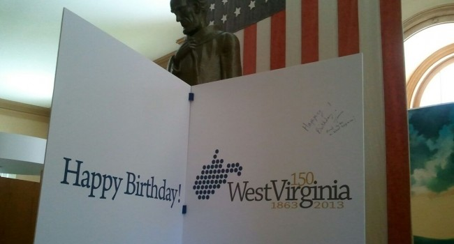 A large birthday card greets visitors at Independence Hall in Wheeling as state celebrates its 150th birthday.