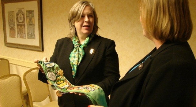 New Girl Scout Black Diamond Council CEO Beth Casey shows off her own Girl Scout sash during Thursday's gathering.