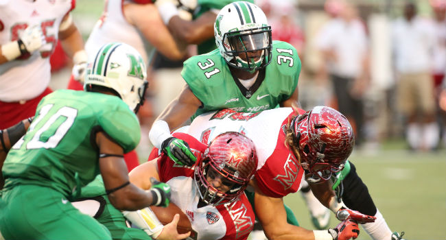 Linebacker Evan McKelvey (31) and Corey Tindal (10) converge on the Miami offense in Marshall's 52-14 win in week one.