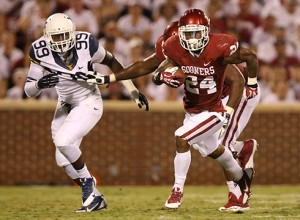 West Virginia's Dontrill Hyman (99) pursues Oklahoma's Brennan Clay last year in Norman. Hyman made two starts as a junior in 2013, registering 18 tackles and 3.5 for loss.