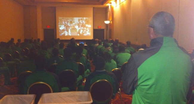 Marshall Coach Doc Holliday and his team watch the annual memorial ceremony via web stream from their hotel in Tulsa where they'll play tonight.