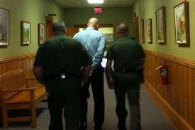 Former Pocahontas County Deputy Bradley Totten, center, was taken away in handcuffs when he was charged last year.