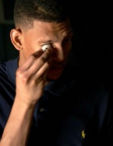 In a still shot from ESPN report, Isaiah Austin removes his prosthetic right eye—an injury he said he hid from all college recruiters except Baylor's.