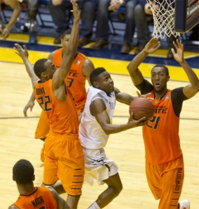 Juwan Staten knifes through Oklahoma State's Markel Brown (22) and Kamari Murphy with 4 seconds left tying to put West Virginia ahead.