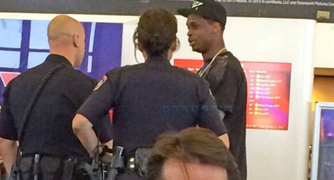 Former WVU quarterback Geno Smith talks with police at LAX before being escorted from the terminal.