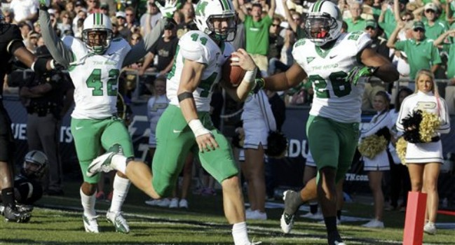 Marshall running back Essray Taliaferro, left, and tight end Gator Hoskins celebrates as safety Derek Mitchell scores a touchdown on a blocked punt against Purdue in 2012.