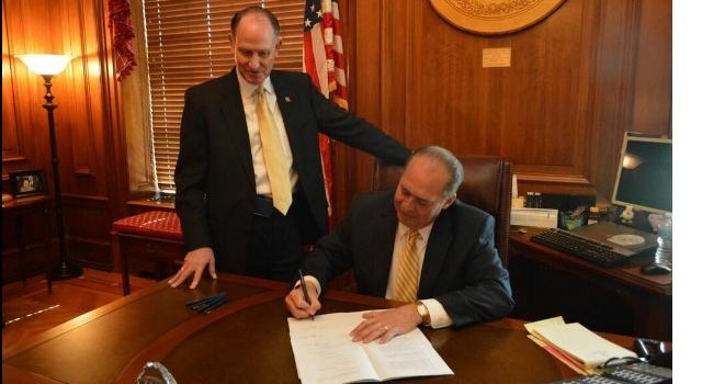 State Senate President Jeff Kessler (standing) watched Gov. Earl Ray Tomblin sign the Future Fund bill into law last week. On Friday, Tomblin still had nearly 90 bills to make decisions on before next Tuesday's deadline.
