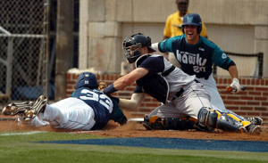 WVU catcher Cameron O'Brien tags out Drew Farber at home after a throw from left fielder Jacob Rice.