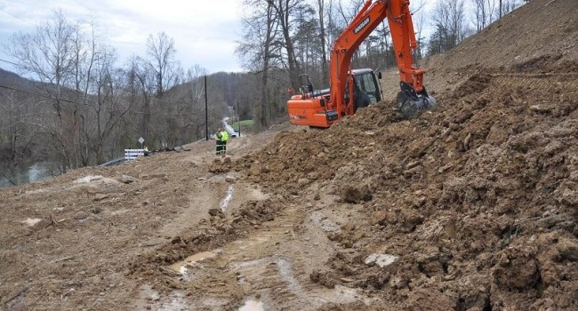 Crews work to clear Coal River Road on Thursday in hopes of eliminating a 20-mile detour for residents.