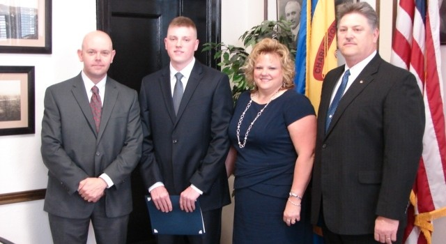 New recruit Jonathon Hill, second from left, is following in his father's footsteps. He stood Thursday with Police Chief Brent Webster, his mother Debbie and father Jerry.