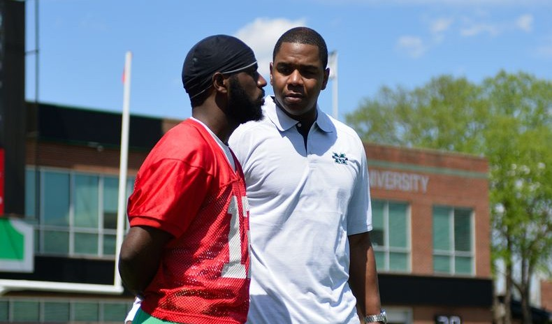 QB Rakeem Cato (12) talks with former Marshall and NFL QB Bryon Leftwich at Saturday's Green/White Game.