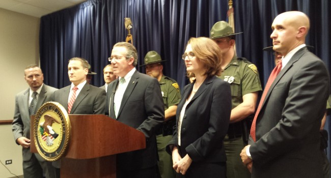 U.S. Attorney Booth Goodwin, center, announced the results of the kickback scheme investigation on May 30.