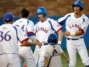 Kansas players mob Tucker Tharp at home plate after his tie-breaking two-run homer in the eighth lifted the Jatyhawks to a 5-3 win Friday night.