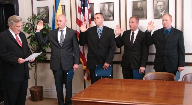 Charleston Mayor Danny Jones (left) swears in four new officers. They'll begin training at the academy next week.