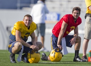 West Virginia quarterbacks Clint Trickett and Skyler Howard (right) take a break during Thursday's practice.