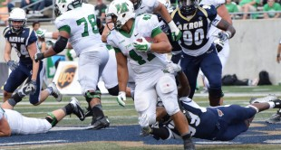Devon Johnson (47) drags defenders with him.