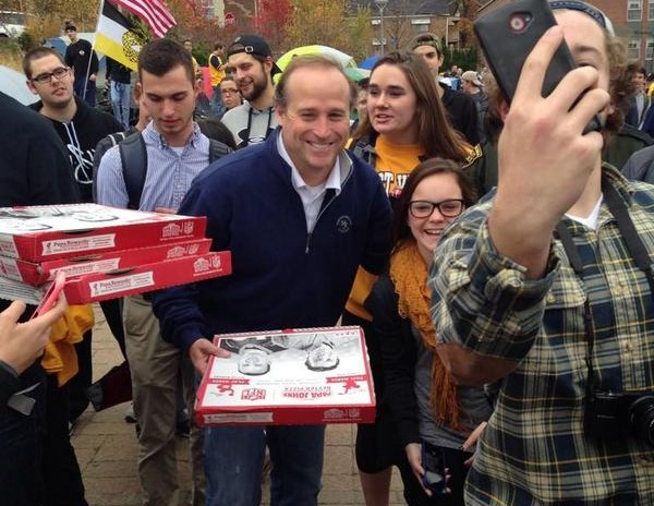 WVU football coach Dana Holgorsen handed out free pizza and posed for dozens of selfies during his visit to Tent City Friday.