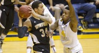 Wofford terriers forward Lee Skinner (34) is guarded by West Virginia Mountaineers guard Daxter Miles Jr. (4) during the first half at the WVU Coliseum.