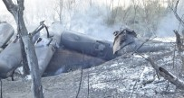 The tanker cars that jumped the track were still smoldering Tuesday afternoon.