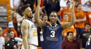 West Virginia point guard Juwan Staten celebrates in front of Oklahoma State's Anthony Allen Jr. during the final minutes of the Mountaineers' 73-63 win in Stillwater, Okla.