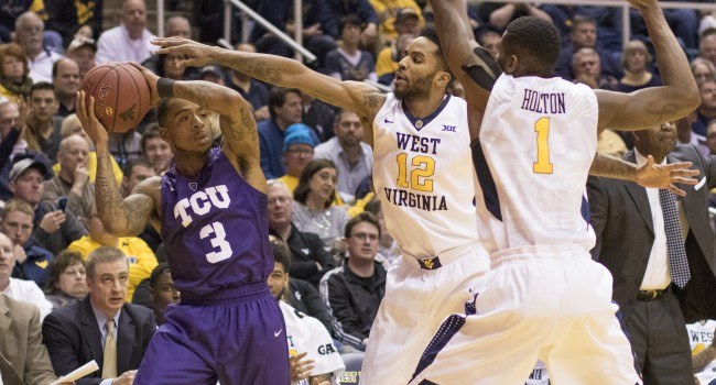 Tarik Phillip and Jonathan Holton trap TCU's Malique Trent during West Virginia's 73-42 win Saturday.  The Frogs committed 26 turnovers.