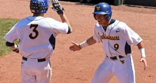 WVU's Kyle Gray (9) celebrates a run by Jimmy Galusky (3) in Sunday's Big 12 tournament championship. TCU won 11-10 in 10 innings.