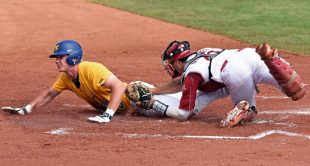 A West Virginia runner slides safely into home during Saturday's 11-1 win over Oklahoma in the Big 12 tournament semifinals.