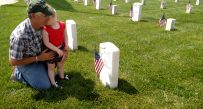 A cemetery employee and his granddaughter visit the graves at the Grafton National Cemetery on Monday.