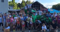 Members of the Thundering Herd football team pause for a group picture with other volunteers distributing supplies in Elkview.
