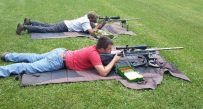 Weston Dunlap, 18, (red shirt) focuses on the target at the White Horse Firearms and Outdoor Education Center