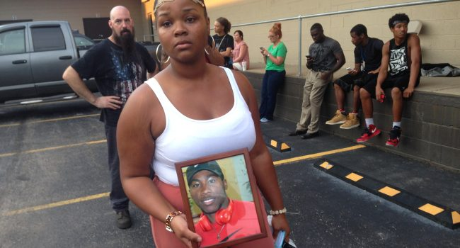Courtney Campbell, a friend who organized the vigil, holding a picture of Dyess.